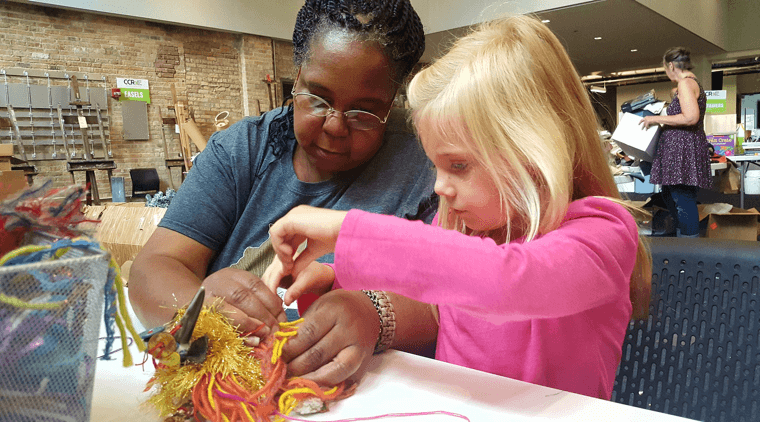 Black older woman guiding a young Caucasian girl in an art project